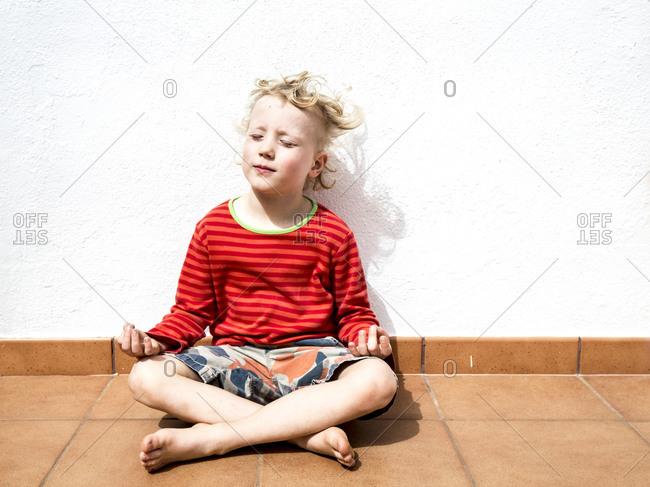 Portrait of blond little boy sitting in lotus position