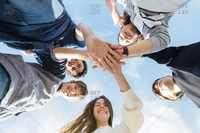 Five friends stacking their hands- seen from below