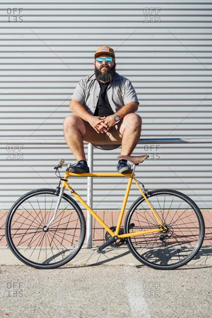 Portrait of bearded man with yellow fixie bike sitting on railing