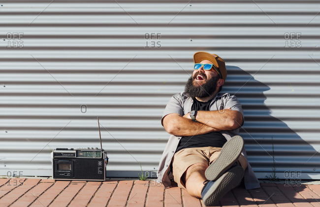Portrait of bearded man with portable radio enjoying sunlight