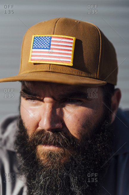Portrait of bearded man wearing baseball cap with American flag