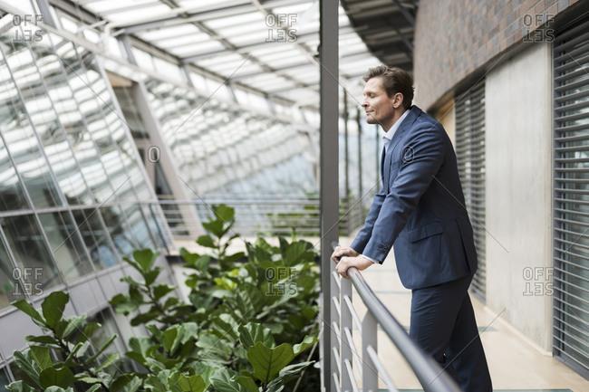 Businessman standing on gallery- enjoying green plants in atrium