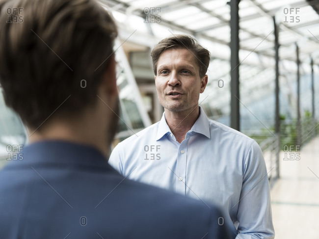 Businessman talking to colleague in atrium of office building