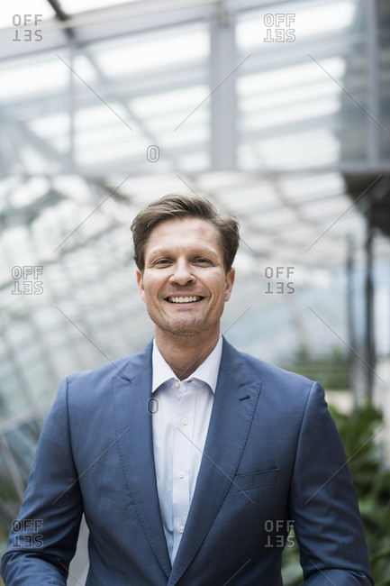 Smiling businessman standing in green atrium- portrait