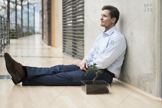 Businessman in green atrium- sitting on gallery
