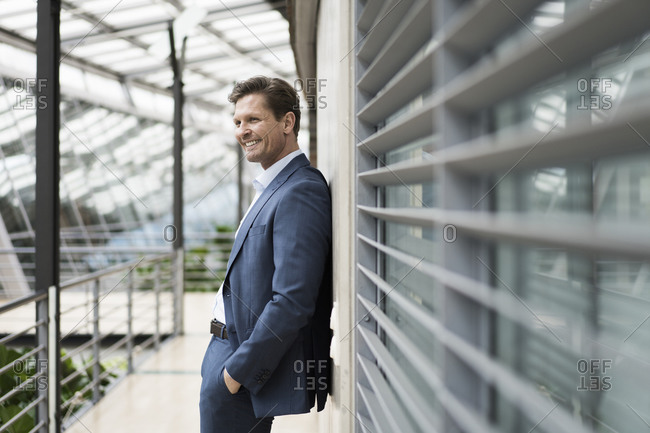Relaxed businessman leaning against wall on gallery of atrium