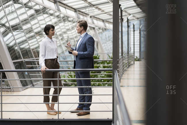 Businessman and woman talking in sustainable office building- using digital tablet