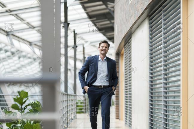 Confident businessman walking on gallery of green atrium