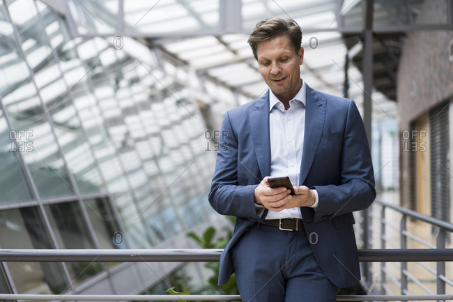 Businessman using smartphone in bright atrium