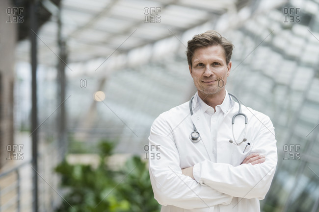 Portrait of doctor with stethoscope- standing in atrium- with arms crossed