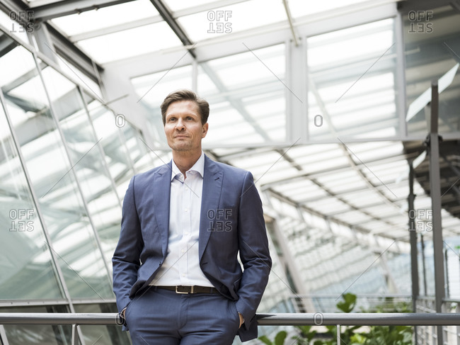 Confident businessman leaning on railing with hands in pockets