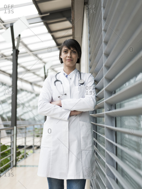 Portrait of female doctor with stethoscope- standing in atrium- with arms crossed