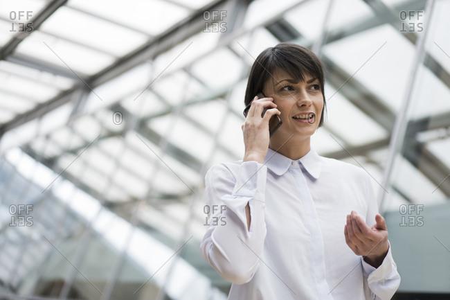 Businesswoman using smartphone in atrium of office building