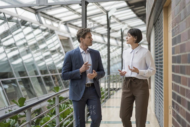Businessman and woman talking in sustainable office building