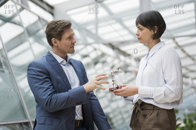 Businessman and woman standing in atrium of office building- talking about robot arm