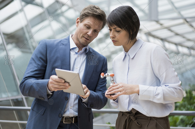 Businessman and woman standing in atrium of office building- using digital tablet- holding robot arm