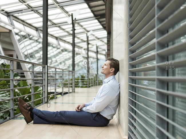 Businessman in green atrium- sitting on gallery- thinking