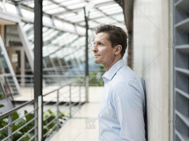 Businessman in green atrium.- leaning on wall