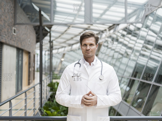 Portrait of doctor with stethoscope- standing in atrium