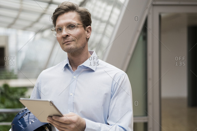 Architect carrying hard hat- using digital tablet