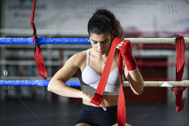Young woman tying bandage around her hand in boxing club