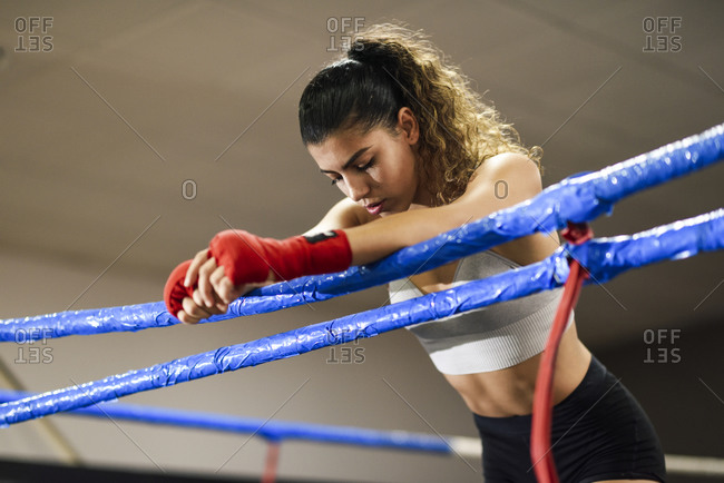 Athletic female boxer in boxing ring leaning on rope concentrating before the fight