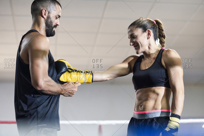 Trainer putting the boxing gloves on a female boxer