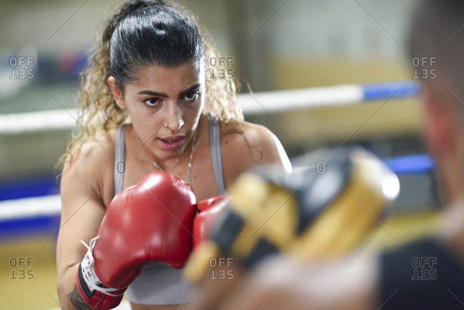 Portrait of focused female boxer sparring with her coach in gym