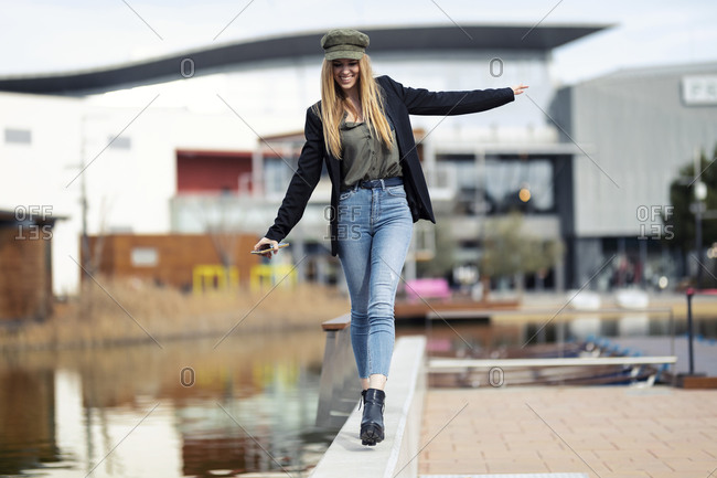 Blond young woman balancing on a wall near water