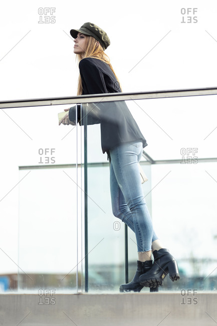 Portrait of blond young woman leaning on railing looking at distance