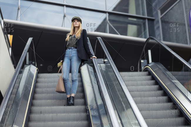 Blond young woman with bag and smartphone standing on an escalator looking at distance