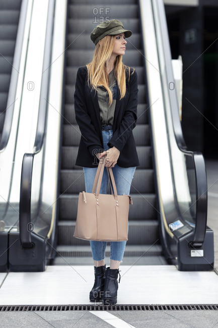 Portrait of blond young woman with bag standing in front on an escalator
