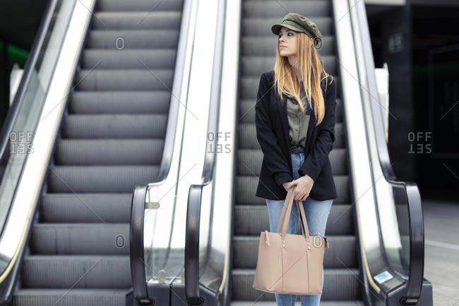Portrait of blond young woman with bag and smartphone standing in front on an escalator