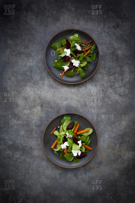 Plates of corn salad with roasted carrot strips- beetroot- Spanish onions and goat cream cheese