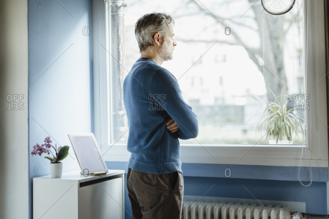 Pensive man standing in living room looking out of window