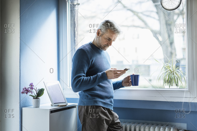 Mature man standing with coffee mug standing in living room looking at smartphone