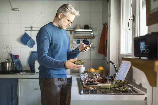 Mature man preparing artichoke in his kitchen looking at smartphone