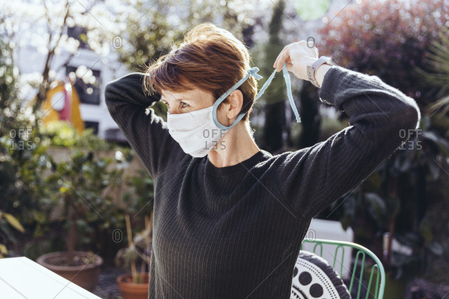 Woman siting in garden- putting on face mask