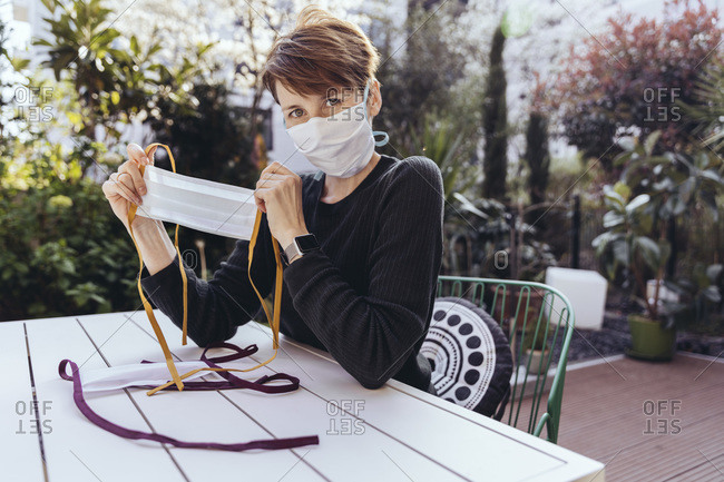 Woman sitting in garden- showing self-made face masks