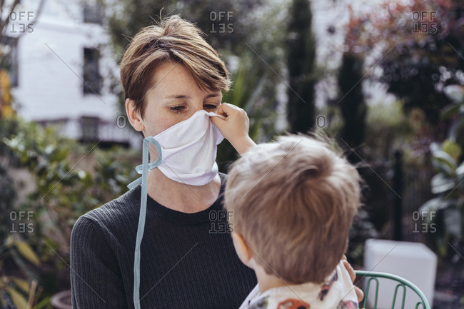 Little boy helping his mother to put on a face mask