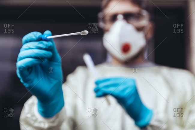 Healthcare worker holding swab test kit for PCR testing