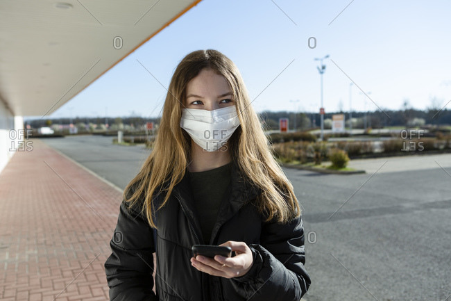 Portrait of girl wearing mask at an empty street- using smartphone