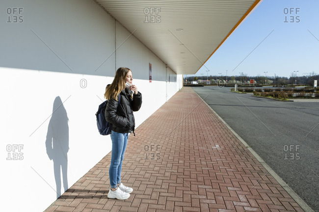 Girl with mask standing at an empty street