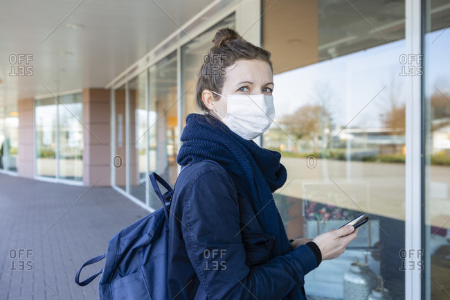 Woman with mask standing in front of a display window of closed shopping center- using smartphone