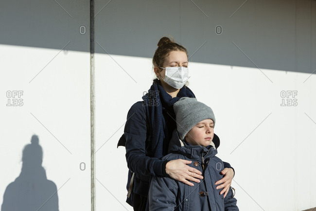 Woman wearing mask standing with son in front of a white wall- eyes closed