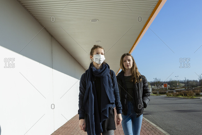 Woman wearing face mask walking with daughter at an empty street