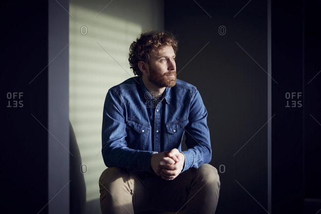 Relaxed casual businessman sitting down looking sideways