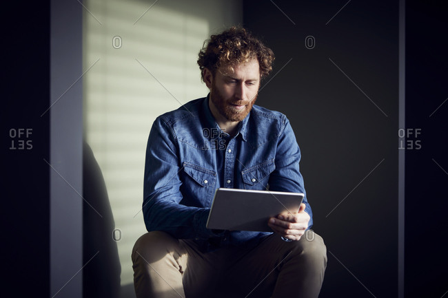 Casual businessman sitting down using a tablet