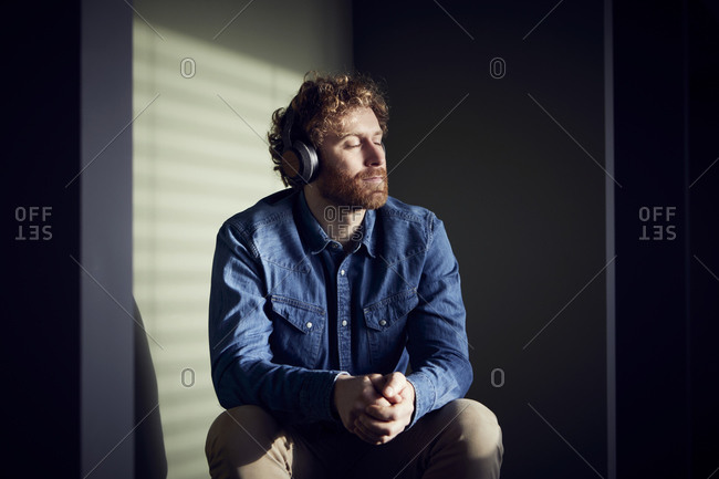 Relaxed casual businessman sitting down listening to music with headphones