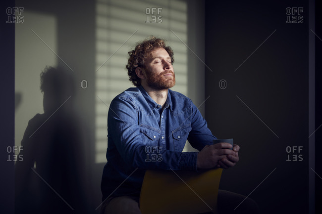 Relaxed casual businessman sitting down with closed eyes
